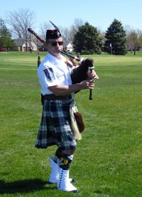 Bagpiper Doug Hardwick leading the ceremony